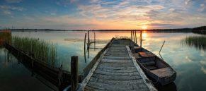 Steg mit Boot im Sonnenuntergang